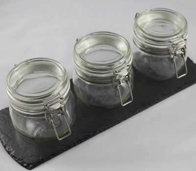 A Black Slate with Three Large Glass Ikea Kilner Jars