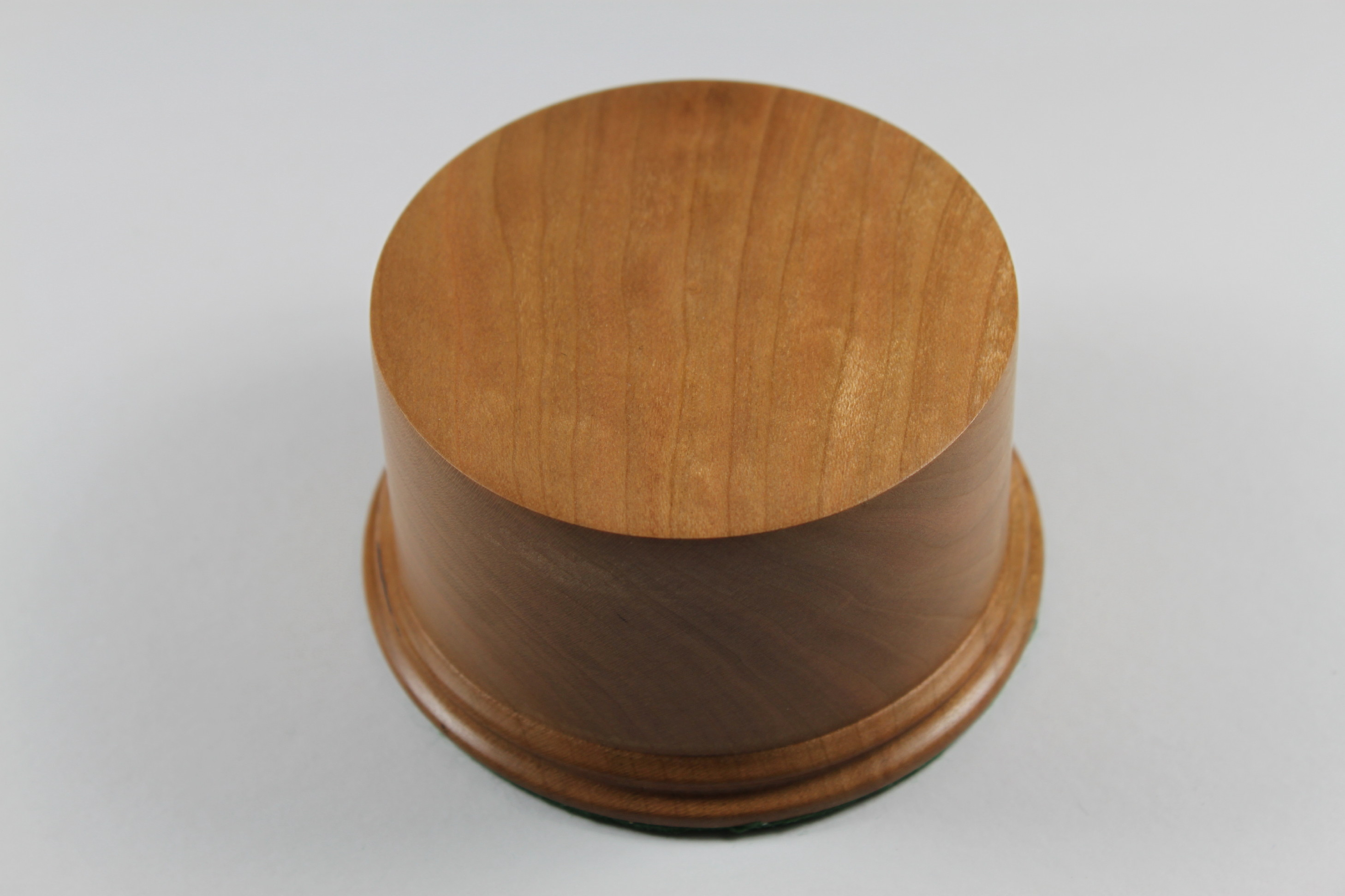 A solid wood Base made from American Cherry 50mm High with a display area of 80mm Diameter